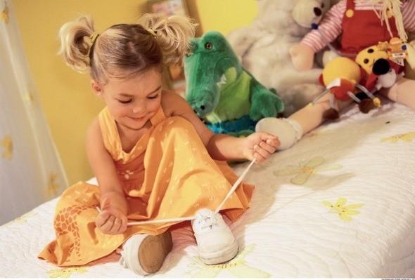 Девочка завязывает шнурки