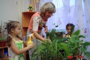 Воспитатель с девочками поливают цветы