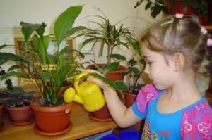 Девочка поливает растение