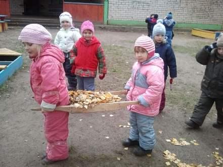 Дети несут сухие листья