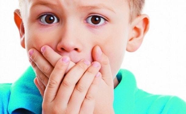 Мальчик скрестил руки на губах