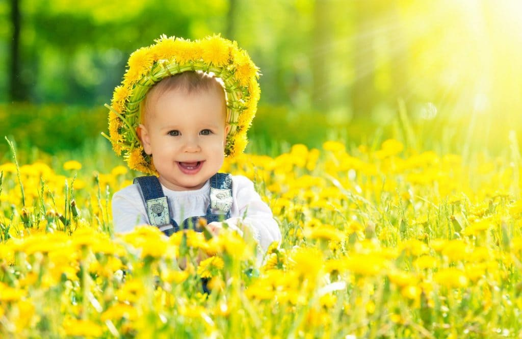 Ребенок в венке в цветах на солнечном свете