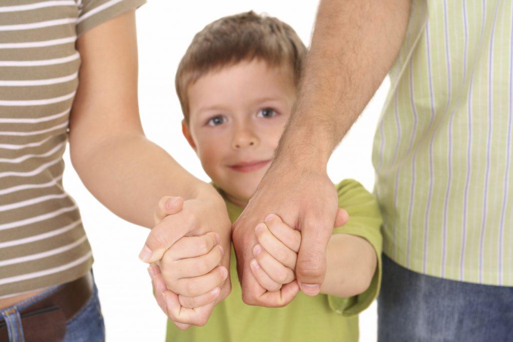 Ребенок за руку с родителями